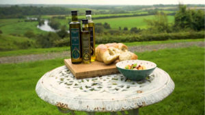 Newgrange Gold Camelina & Rapeseed Oil on table with bread above Boyne Valley
