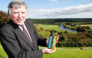 John Rogers at Newgrange Gold holding bottles of camelina oil in front of boyne valley