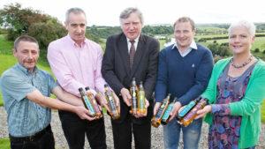 Newgrange Gold team holding out bottles of Newgrange Gold rapeseed and camelina oils