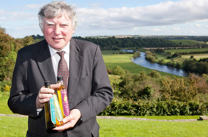 John Rogers holding bottles of Newgrange Gold rapeseed oil above river Boyne