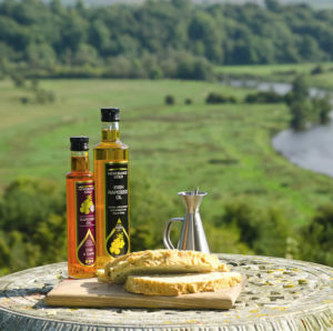Bottle of Newgrange Gold rapeseed chilli & garlic oil and camelina oil on table overlooking Boyne valley