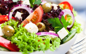 Green salad with tomato, olives, red onion and newgrange gold oil drizzled over