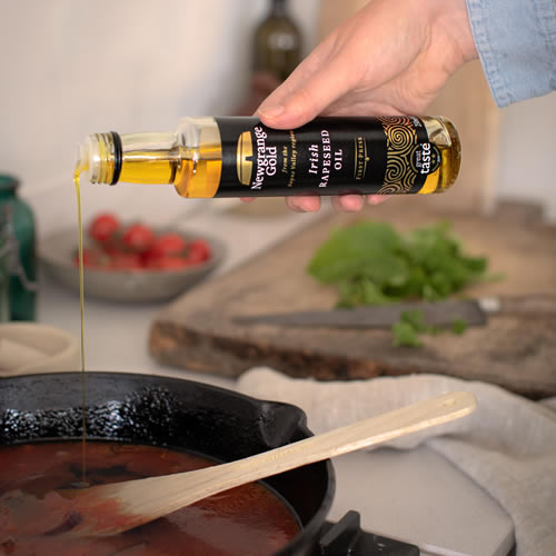 Someone pouring Newgrange Gold Irish rapeseed oil into frying pan