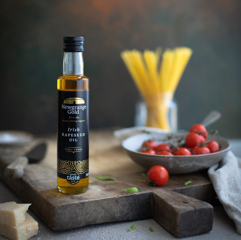 Newgrange Gold Irish Rapeseed Oil with bowl tomatoes and pasta in background